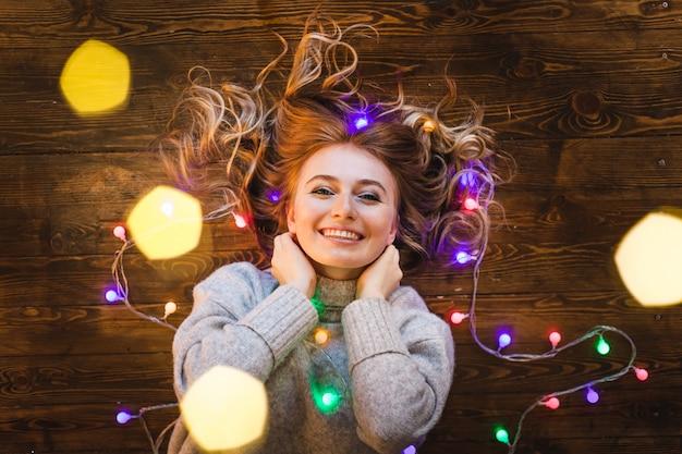 Ragazza con un maglione lungo e leggero, una giacca e una ghirlanda con luci natalizie Foto Premium