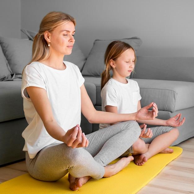 Ragazza e mamma meditando Foto Premium
