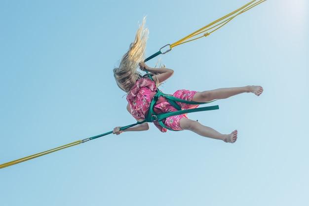 Ragazza in abito multicolore cade su un'attrazione contro il cielo. Foto Premium