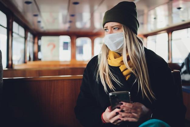 Una ragazza con una maschera protettiva in un vagone della metropolitana con un telefono cellulare in mano Foto Premium