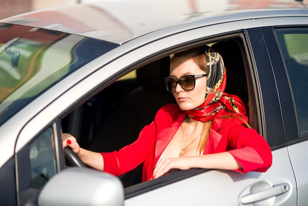 Ragazza in rosso e occhiali da sole alla guida di un'auto. signora di affari in auto, indossando occhiali da sole Foto Premium