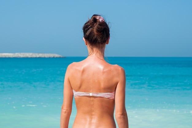 La ragazza è tornata in costume da bagno contro il muro del mare e del cielo blu Foto Premium