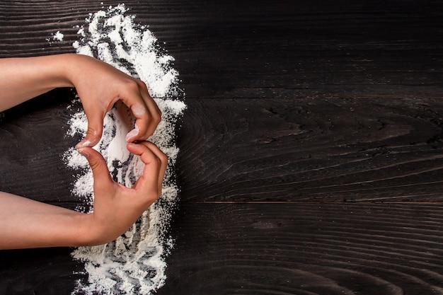Le mani della ragazza a forma di cuore con farina sul tavolo nero scuro, sfondo del menu ricetta alimentare. posto per il testo. formato banner lungo Foto Premium