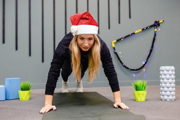 Una ragazza in un cappello di babbo natale facendo esercizi di fitness in palestra Foto Premium