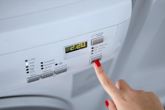 La ragazza imposta il programma di lavaggio per la lavatrice. Foto Premium