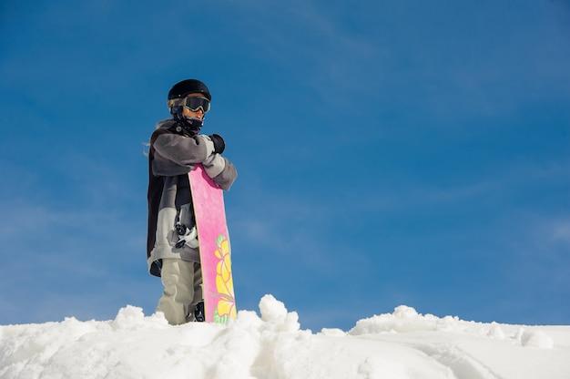 Ragazza in occhiali da sci e attrezzatura da sci si trova nella neve contro il cielo blu Foto Premium