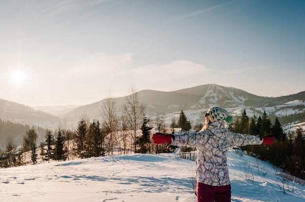 Ragazza in piedi indietro e guarda le montagne innevate d'inverno. ama il paesaggio. cammina nella natura. stagione del gelo. tempo freddo, neve sulle colline. escursionismo. alpinista in cima in una soleggiata giornata invernale. Foto Premium