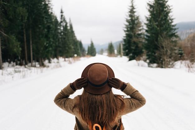 Una ragazza si trova su una strada forestale innevata, una vista dal retro Foto Premium