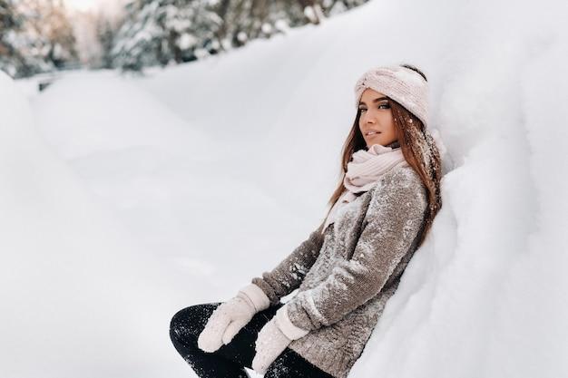 Una ragazza con un maglione e guanti in inverno si trova su uno sfondo innevato. Foto Premium