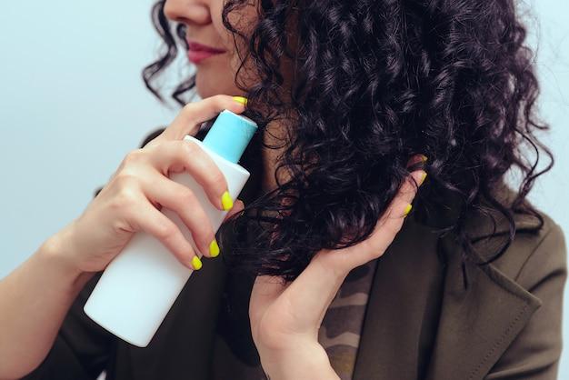Ragazza che usando spray per fare acconciatura riccia Foto Premium