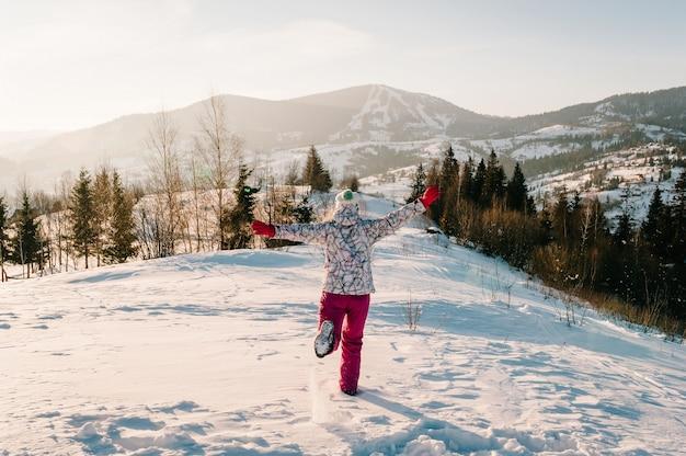Ragazza che cammina indietro e guarda le montagne innevate dell'inverno. ama il paesaggio. cammina nella natura. stagione del gelo. tempo freddo, neve sulle colline. escursionismo. alpinista in cima in una soleggiata giornata invernale. Foto Premium