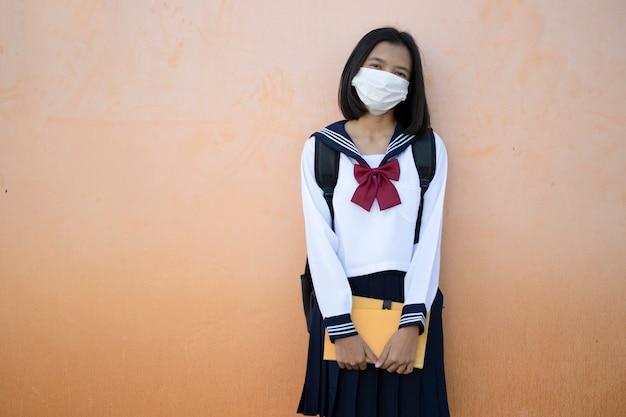 Ragazza indossa uniforme e maschera tenere il libro Foto Premium