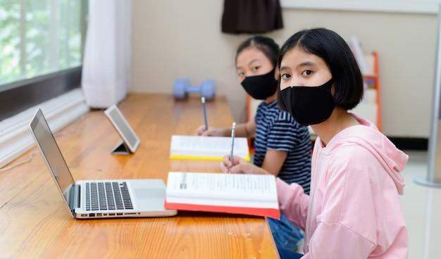 Ragazza che indossa una maschera igienica, studiando da uno schermo di computer a casa Foto Premium