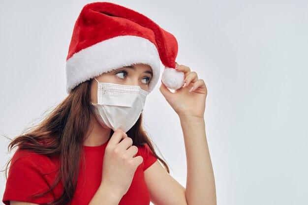 Ragazza che indossa la mascherina medica che tiene la maglietta rossa del cappello della santa vista ritagliata Foto Premium