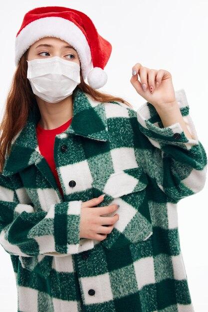 Ragazza che indossa una maschera medica vestiti di capodanno vacanze di natale. foto di alta qualità Foto Premium