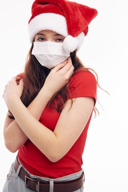 La ragazza che indossa una maschera medica vestiti di capodanno natale vacanza sfondo chiaro Foto Premium
