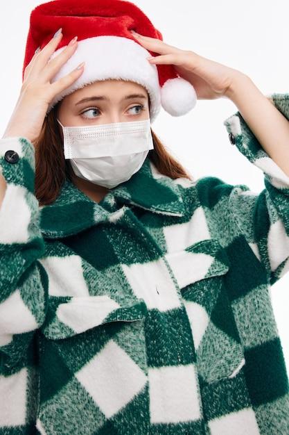 Ragazza che indossa il primo piano di vacanza del cappotto del plaid della maschera medica del cappello della santa Foto Premium
