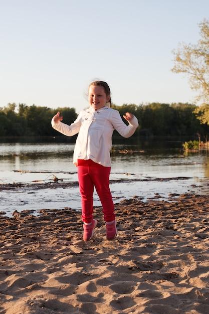 Una ragazza in giacca bianca e pantaloni rosa salta sulla sabbia sulla spiaggia in riva al fiume durante il tramonto. Foto Premium