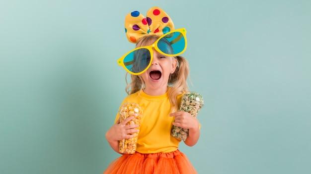 Ragazza con grandi occhiali da sole e caramelle nelle sue mani Foto Premium