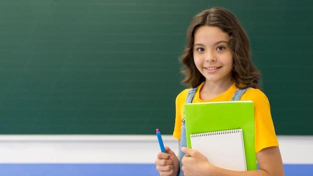 Ragazza con libri in classe Foto Premium