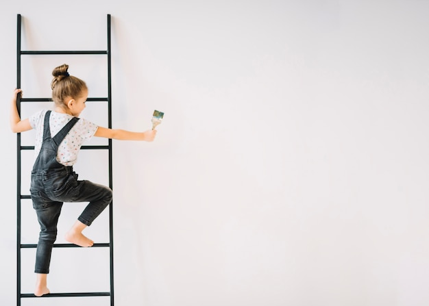 Ragazza con la spazzola sulla scala vicino alla parete Foto Premium