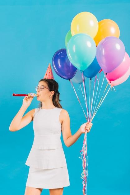 Ragazza con palloncini colorati che soffia corno di partito su sfondo blu Foto Premium