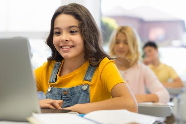 Ragazza con il portatile a scuola Foto Premium