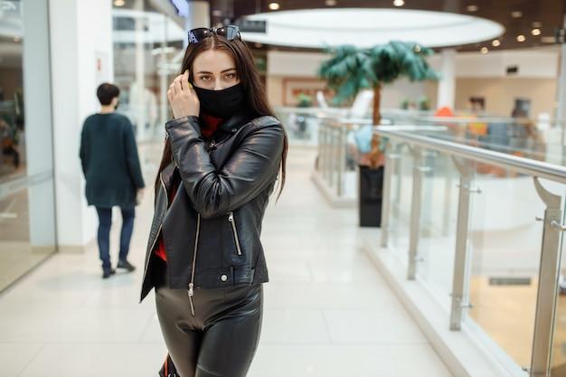 Una ragazza con una maschera medica nera sta camminando lungo un centro commerciale. pandemia di coronavirus. una ragazza in una maschera protettiva sta facendo shopping al centro commerciale Foto Premium