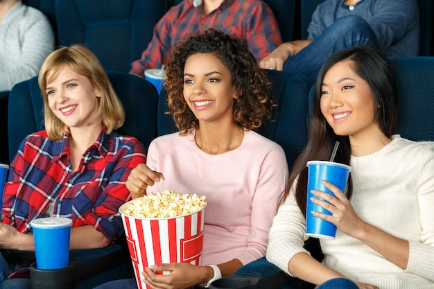 Ragazze fuori serata belle ragazze che mangiano popcorn e che guardano insieme un film Foto Premium