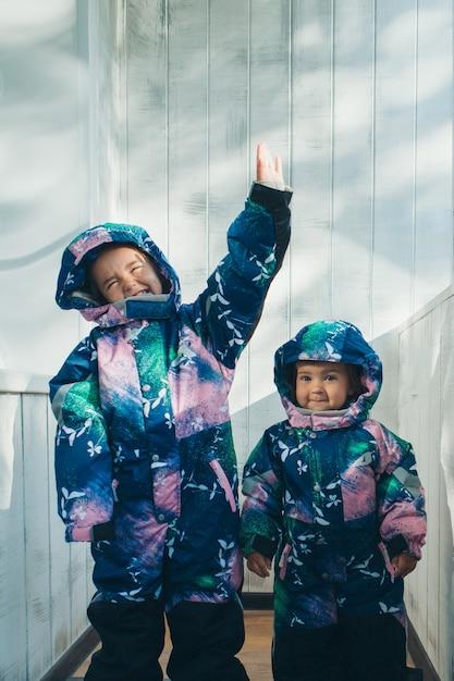 Ragazze con le stesse tute calde. abbigliamento invernale per bambini di tutte le età Foto Premium