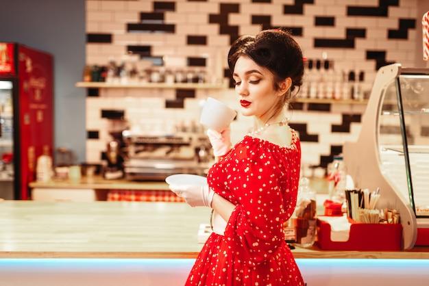 Glamour pin up girl con trucco beve caffè in retro cafe, 50 moda americana. abito rosso con pois, stile vintage Foto Premium