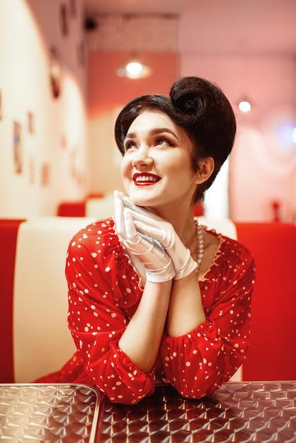 Glamour pin up girl con labbra rosse che si siede nel retro caffè, 50 moda americana. abito a pois, stile vintage Foto Premium