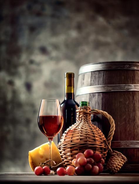 Bicchiere, bottiglia, caraffa di vino e botte Foto Premium