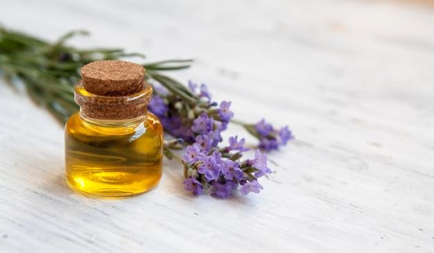 Bottiglia di vetro riempita con olio di lavanda. cosmetici naturali, concetto di erboristeria Foto Premium
