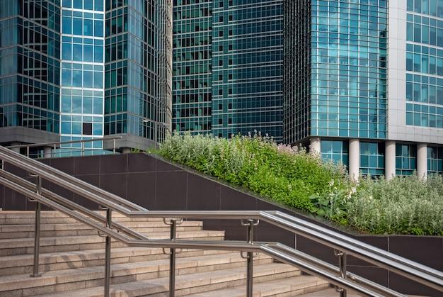 Edifici in vetro, scale e piante verdi nel quartiere degli affari Foto Premium