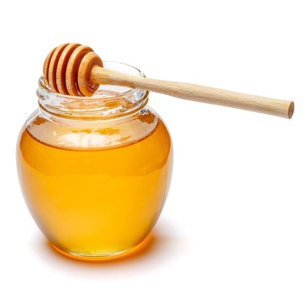 Barattolo di vetro pieno di miele e bastone di legno su uno spazio bianco. tracciato di ritaglio Foto Premium