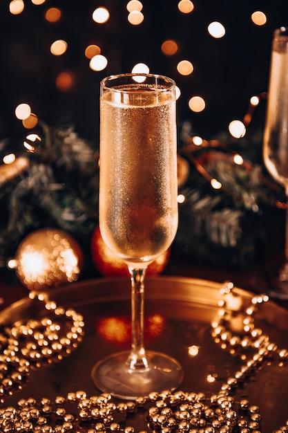 Un bicchiere di champagne freddo in un'atmosfera natalizia Foto Premium
