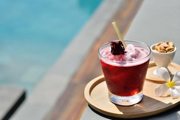 Bicchiere di succo di roselle freddo sul bordo di una piscina Foto Premium