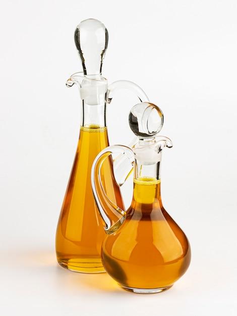 Decanter di vetro con verdura e olio d'oliva isolato su bianco Foto Premium