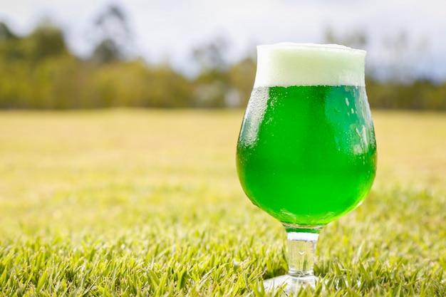 Bicchiere di birra verde sul prato per celebrare il giorno di san patrizio. Foto Premium