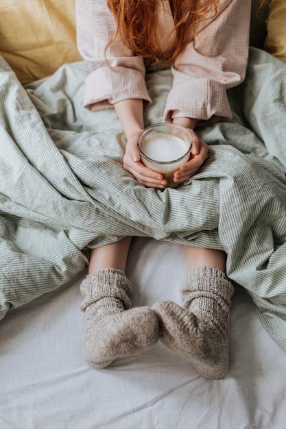 Un bicchiere di caffè caldo con schiuma di latte, che la ragazza tiene tra le mani, seduta a letto in calzini caldi. Foto Premium