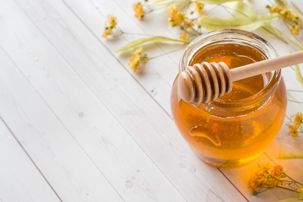 Vaso di vetro di miele, fiori di tiglio Foto Premium