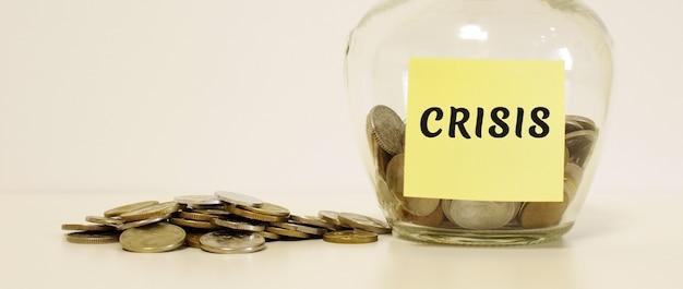 Vaso di vetro con monete. l'iscrizione sul foglio per appunti crisis. concetto finanziario. Foto Premium