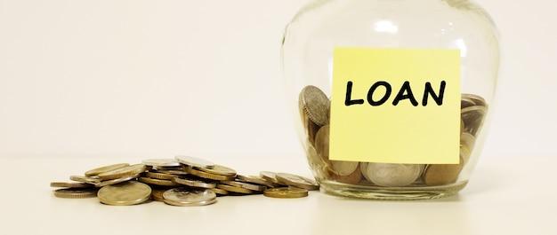Barattolo di vetro con monete per il risparmio. l'iscrizione sulla nota carta prestito. concetto finanziario. Foto Premium