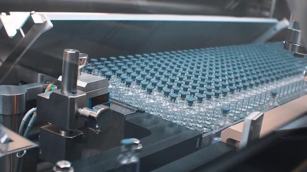 Bottiglie mediche di vetro nella produzione farmaceutica per la produzione di vaccini e prodotti medici. coronavirus Foto Premium