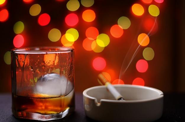 Un bicchiere di on the rock con sigaretta nel portacenere Foto Premium