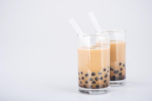 Un bicchiere di tè dolce al latte con perle di tapioca e paglia su sfondo bianco. copia spazio Foto Premium