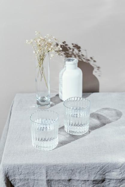 Bicchiere d'acqua e vaso con fiori Foto Premium