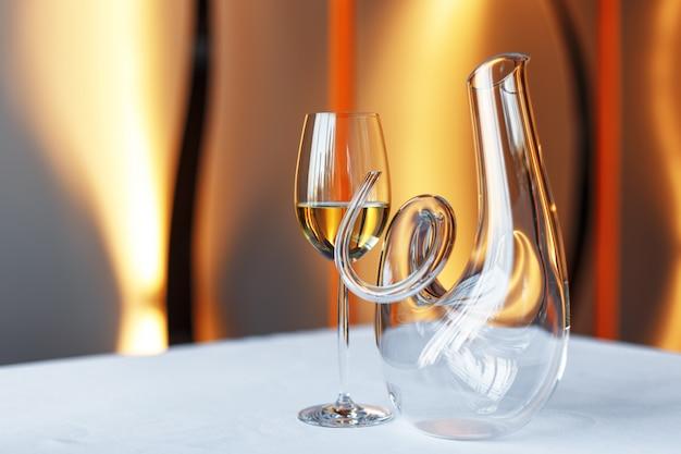 Bicchiere di vino e un decantatore su una tavola con una tovaglia bianca. Foto Premium