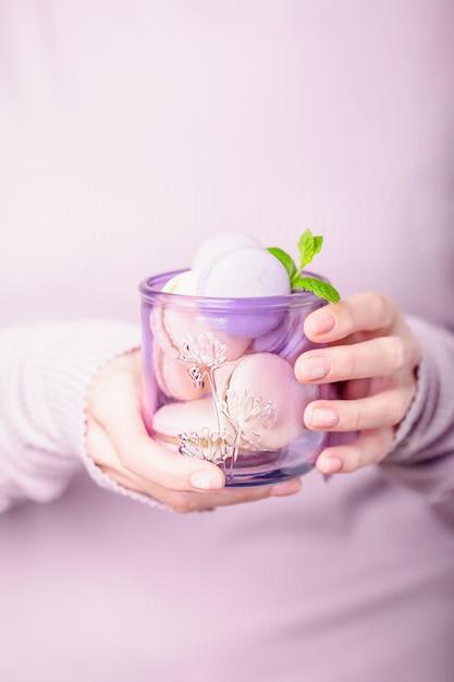 Bicchiere con amaretti in mano, vetreria in vetro riciclato Foto Premium
